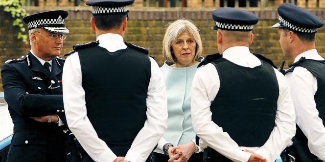 La ministre de l'intérieur Theresa May s'entretient avec des policiers, qui devront dorénavant coopérer avec  des sociétés de sécurité privées. -