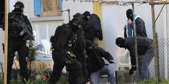 Des policiers escortent l'une des personnes interpellées à Nantes, le 30 mars 2012.