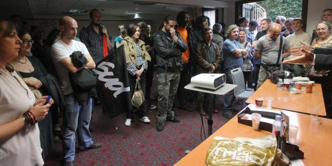 Des employés parisiens demandent des explications sur les salaires au directeur régional (bras tendus, à droite) durant une réunion de négociation, le 29 mars.