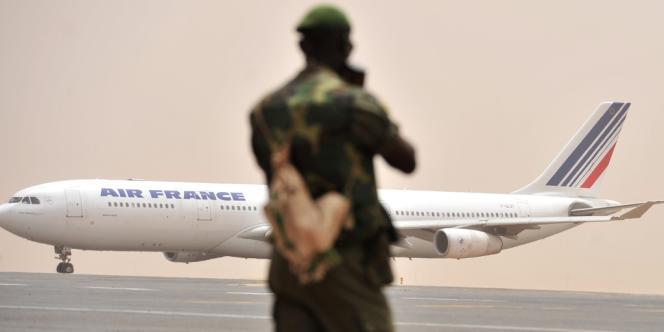 Un militaire malien observe un avion d'Air France sur l'aéroport de Bamako, le 29 mars 2012.