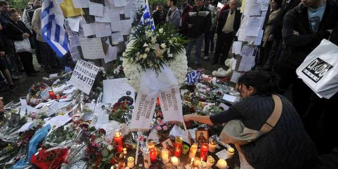 Des Grecs se recueillent, le 5 avril, sur le lieu où un retraité s'est donné la mort la veille, sur la place Syntagma à Athènes.