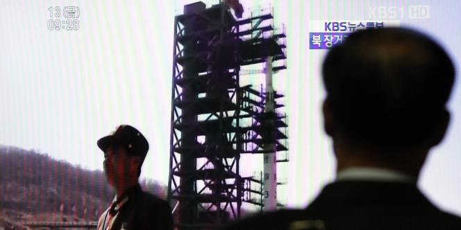Un passant à Séoul devant un écran de télévision annonçant le lancement de la fusée Unha-3, le 13 avril 2012.