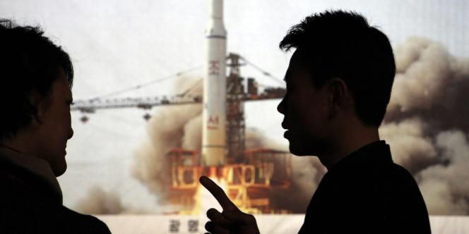 Un guide nord-coréen discute avec une journaliste étrangère devant une photo du lancement de fusée de 2009.