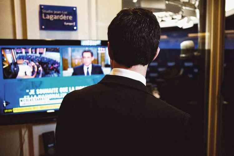 """En haut, Manuel Valls (de dos) est l'invité d'Europe 1 mardi 13 mars, au lendemain du premier sondage donnant François Hollande derrière Nicolas Sarkozy au premier tour de la présidentielle. A Bruce Toussaint qui l'interroge, il répond : """"Rien n'est fait."""" En bas, le directeur de  la communication du candidat socialiste, lors d'un déplacement à Marseille, mercredi 14 mars. Devant lui, Faouzi Lamdaoui, chef de cabinet de François Hollande, et Aquilino  Morelle (écharpe rouge), directeur adjoint de la campagne.Photo:Christopher Morris/VII pour M Le magazine du Monde"""