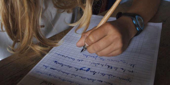 Un élève de CM2 écrit une dictée le 08 juin 2007 sous le préau de l'école primaire du Puits Picard, à Caen.