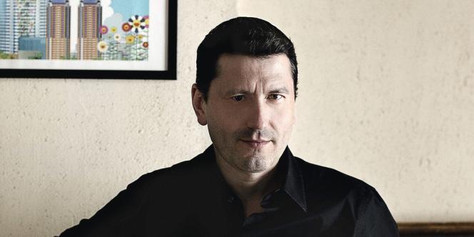 Frédéric Martel, chez lui, devant une affiche de Takashi Murakami.
