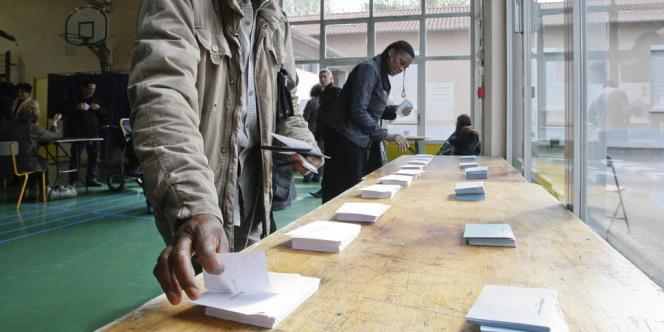 Des électeurs s'apprêtent à glisser leurs bulletins dans l'urne dans un bureau de vote à Vaulx-en-Velin.