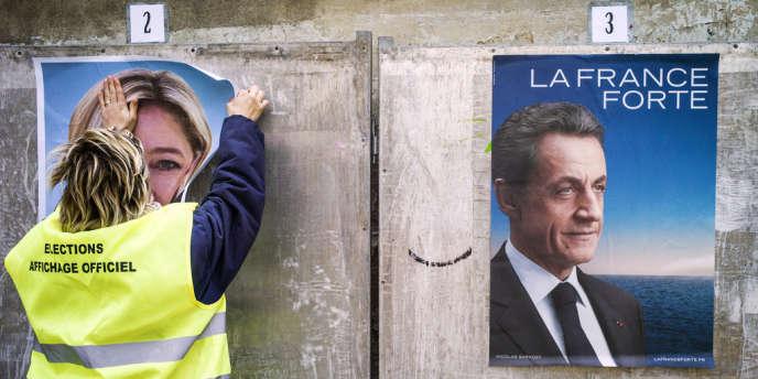 Une employée colle les affiches de campagne des candidats à la présidentitelle de 2012.