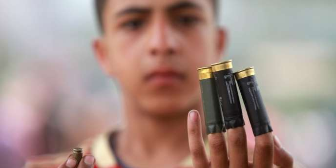 Un jeune homme tient des douilles retrouvées après les affrontements qui ont fait au moins 20 morts au Caire, mercredi 2 mai.
