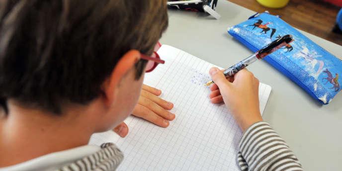 Un élève écrit sur cahier dans l'une des classes de l'école Harouys à Nantes, le 05 septembre 2011, jour de la rentrée scolaire.