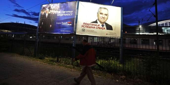 Un passant devant des panneaux électoraux, à Belgrade. A gauche sur l'affiche : Boris Tadic, à droite, Tomislav Nikolic, le 6 mai 2012.