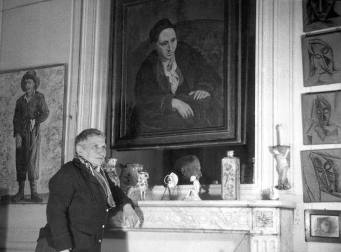 La romancière Gertrude Stein devant un portrait peint par Picasso (1906) dans son appartement parisien.