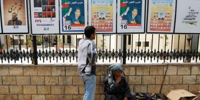 Un vendeur de rue devant des panneaux électoraux, à Alger, le 9 mai.