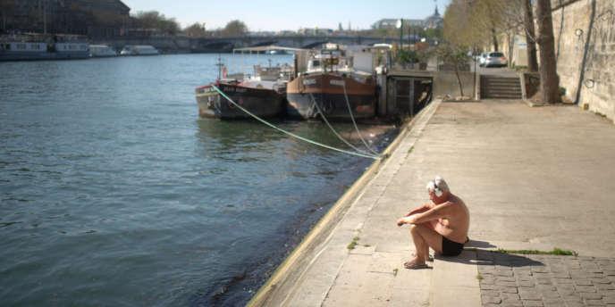 Un homme en maillot de bain prend le soleil sur les berges de Seine, le 26 mars 2012.