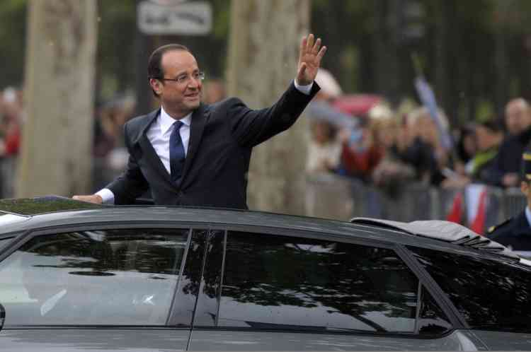 France's new President Francois Hollande waves to the crowd as he rides in his car on the Champs Elysees Avenue after the handover ceremony in Paris, May 15, 2012   REUTERS/Philippe Wojazer  (FRANCE - Tags: POLITICS)