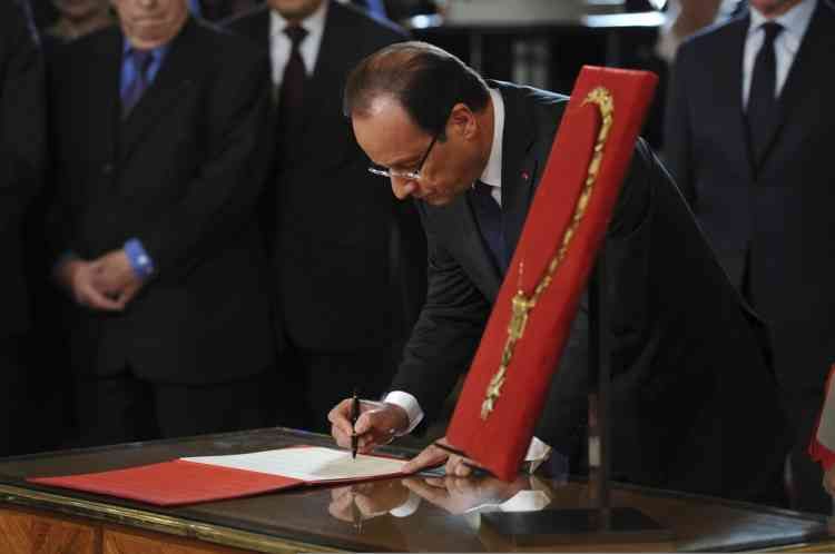 """France's new President Francois Hollande signs a document after being awarded """"Grand Maitre"""" in the Order of the Legion of Honour,  at the investiture ceremony at the Elysee Palace in Paris May 15, 2012.   REUTERS/Bertrand Langlois/Pool    (FRANCE - Tags: POLITICS)"""