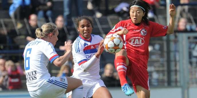 Les Lyonnaises Laura Georges et Amandine Henry face à la Japonaise de Potsdam, Yuki Nagasato, lors de la demi-finale de la Ligue des champions 2012.