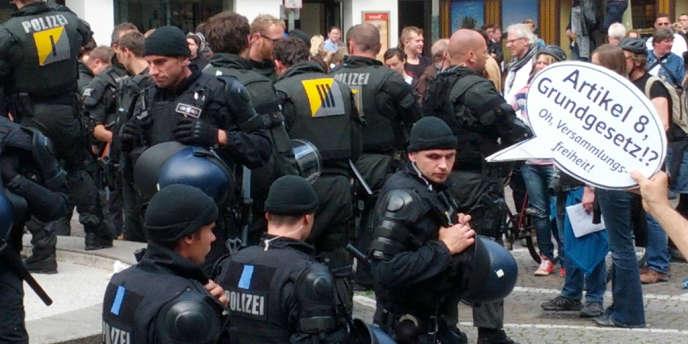 Un homme s'amuse à placer cette bulle de BD au-dessus des policiers :