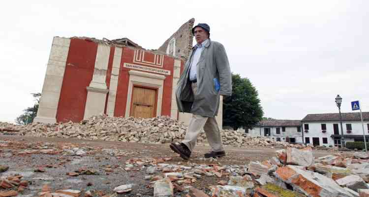 A resident walks in front of the collapsed San Martino church, in Buonacompra, near  Cento, northern Italy, Sunday, May 20. 2012. A magnitude 6  earthquake shook northern Italy early Sunday at 4:04 a.m. Sunday between Modena and Mantova, about 35 kilometers (22 miles) north of Bologna at a relatively shallow depth of 10 kilometers (6 miles). (AP Photo/Luca Bruno)