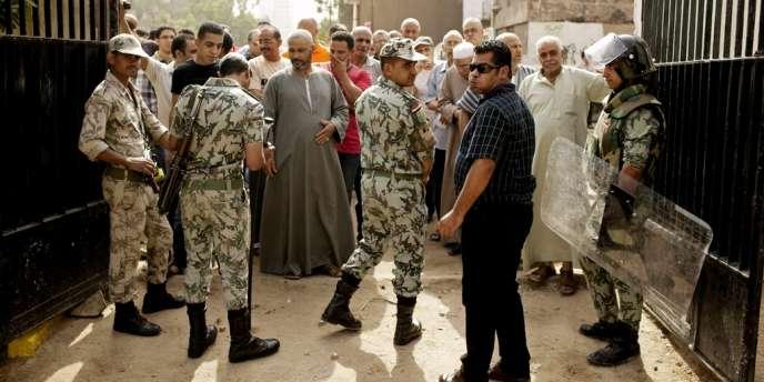 Des policiers surveillent un bureau de vote dans une banlieue dans le sud du Caire, mercredi 23 mai.