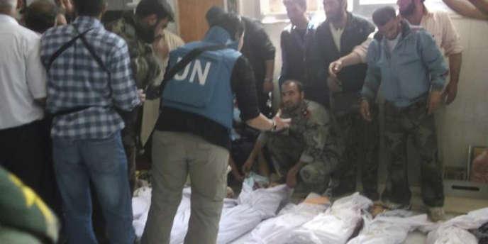 Des membres de l'Armée syrienne libre parlent à un observateur de l'ONU, à côté de corps de victimes du massacre de Houla.