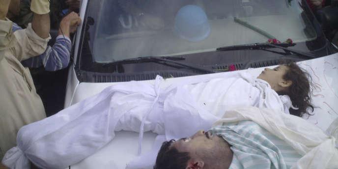 Image diffusée par l'opposition syrienne montrant les corps d'une enfant et d'un homme disposés sur le capot d'une voiture des observateurs de l'ONU, à Houla, le 26 mai.