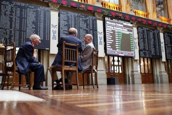 Des courtiers discutent en face des écrans d'information à la Bourse de Madrid. Jeudi 10 juillet, l'indice phare de cette place a reculé de 1,98 %.