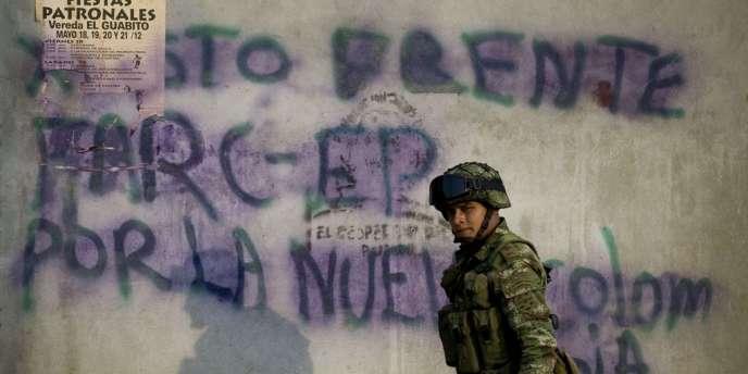 Un soldat marche devant un graffiti