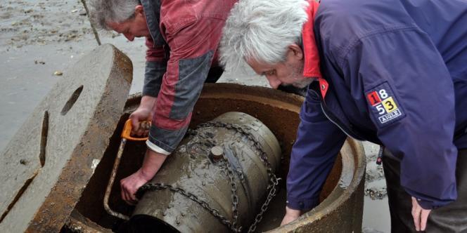 L'ostréiculture Joël Dupuch (à gauche) et le directeur général et vinificateur du Château Larrivet Haut-Brion récupèrent la barrique de vin, après six mois d'immersion dans un parc à huîtres du bassin d'Arcachon.