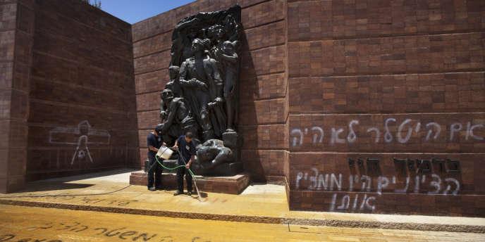 Des agents d'entretien tentent d'effacer les graffitis pronazis découverts, lundi 11 juin, à l'intérieur de Yad Vashem, le mémorial de la Shoah à Jérusalem.