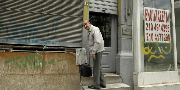Un homme ferme son commerce, à Athènes, le 29 mai. Sur la devanture adjacente, un panneau indiquant un magasin