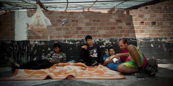 Un groupe de réfugiés s'abrite de la chaleur sous une tente. Le 19 mai et les 3 jours qui ont suivi l'usine a été prise d'assaut à la suite d'une altercation. Une fois le calme retrouvé les policiers sont revenus pour chasser les migrants, pour la plupart afghans.