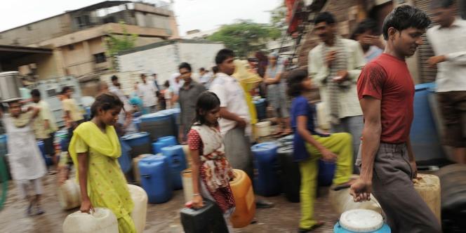 Des habitants de New Delhi remplissent des conteneurs d'eau, en juillet 2009, alors que la ville, comme chaque été, connaît des coupures d'eau.