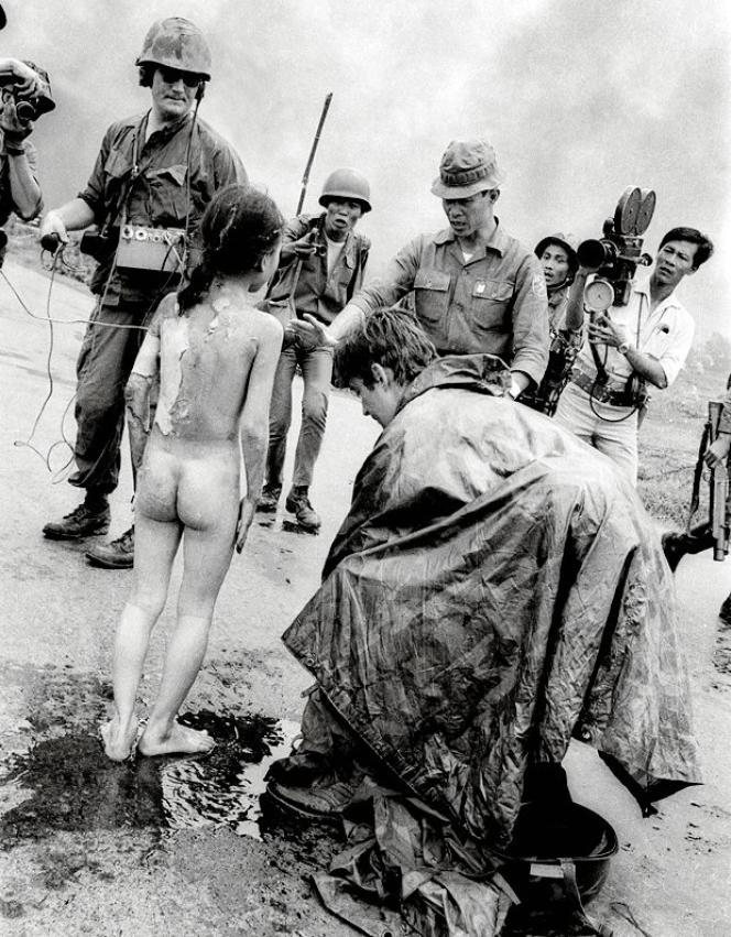 Le 8 juin 1972 sur la route 1. Le journaliste Christopher Wain (à droite, accroupi) avait aspergé d'eau le corps brûlé de la petite fille.