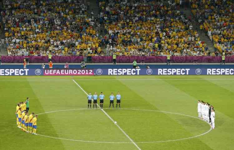 France's (R) and Sweden's players observe a minute of silence in tribute to commentator Thierry Roland, who died on Saturday aged 74, before their Group D Euro 2012 soccer match at Olympic stadium in Kiev, June 19, 2012.          REUTERS/Darren Staples (POLAND  - Tags: SPORT SOCCER)