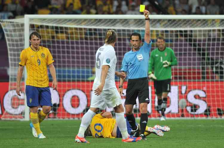 French defender Philippe Mexes (C) is given a yellow card by the referee during the Euro 2012 football championships match Sweden vs France on June 19, 2012 at the Olympic Stadium in Kiev. AFP PHOTO / GENYA SAVILOV