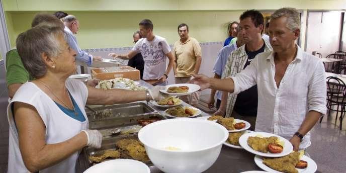 Des volontaires distribuent des repas à Valence (Espagne). Cette région de la côte Est du pays ploie sous une dette équivalant à 20,2 % de son PIB et doit affronter au second semestre des échéances de remboursement de 2,88 milliards d'euros.