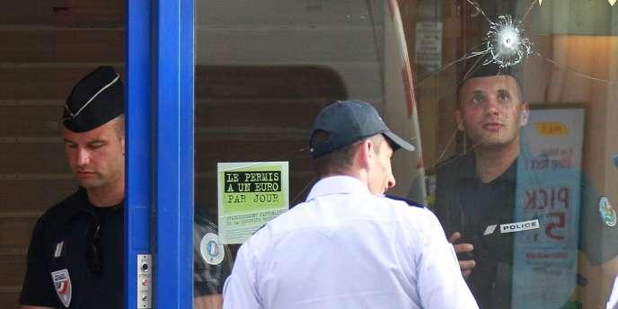 Un policier regarde un impact de balle sur la vitrine de la banque CIC où a eu lieu la prise d'otages et l'assaut mercredi à Toulouse.