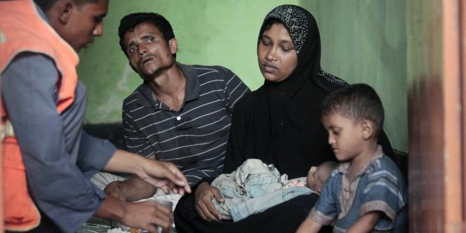 Un garde-côte bangladais sert de la nourriture à une famille de réfugiés rohingya, le 19 juin.