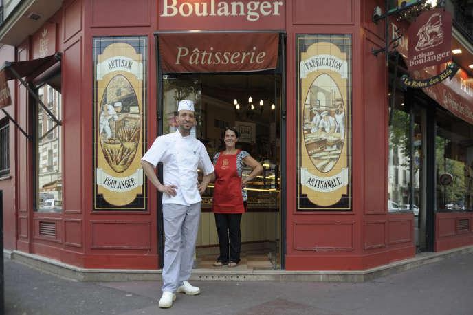 Abdel Nasser Korchani, ici avec une employée, Rosita, devant sa boulangerie de Clichy-la-Garenne (Hauts-de-Seine). Il a décoré l'entrée de sa boutique de faïences qui reproduisent une scène de boulangerie du début du siècle.