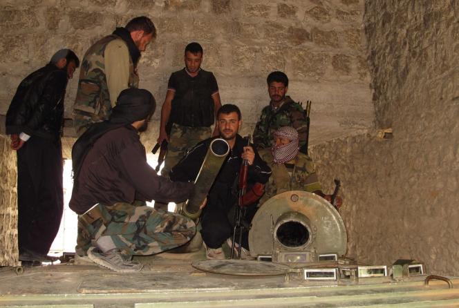 Des membres de l'Armée syrienne libre inspectent un blindé capturé, le 24 juin.