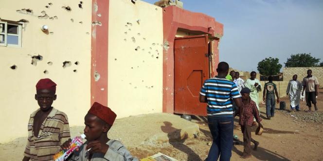 Des habitants du quartier de Danbare, dans la ville de Kano, au Nigeria, passent devant un immeuble criblé de balles.