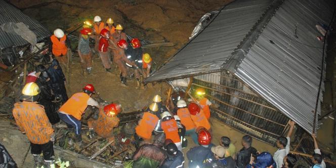 Des secouristes autour d'une maison touchée par le glissement de terrain, le 26 juin à Chittagong, au Bangladesh.