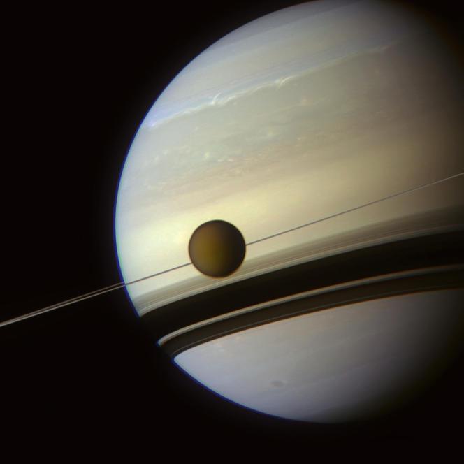 Titan, photographiée le 6 mai par la sonde Cassini alors qu'elle se trouvait dans l'axe des anneaux de Saturne, dont l'ombre se projette sur la géante gazeuse.