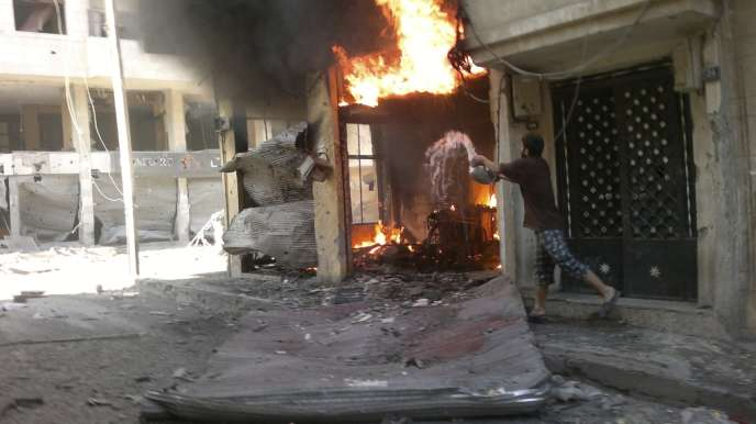 Un habitant de Homs essaie d'éteindre un bâtiment incendié par un bombardement le 1er juillet 2012.