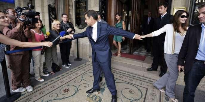 Nicolas Sarkozy serre la main d'une femme en quittant, au bras de sa femme Carla Bruni-Sarkozy, l'hôtel Regina, à Paris, où il a rencontré Aung San Suu Kyi, le 28 juin.