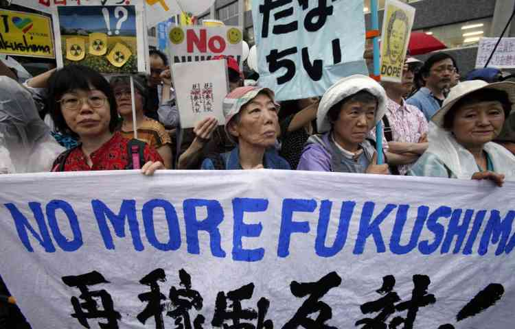 "Protesters stage a rally against the restart of a nuclear reactor, near Prime Minister Yoshihiko Noda's office in Tokyo, Friday, July 6, 2012. A nuclear reactor in western Japan begun generating electricity, Thursday July 5, in the first restart since last year's tsunami led to a nationwide nuclear power plant shutdown. The banner reads: ""Against the restart of a reactor."" (AP Photo/Koji Sasahara)"