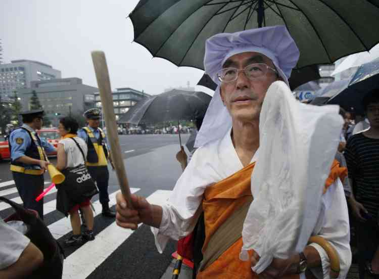 A Buddhist monk beats a drum during a rally against the restart of a nuclear reactor, near Prime Minister Yoshihiko Noda's office in Tokyo, Friday, July 6, 2012. The nuclear reactor in western Japan begun generating electricity, Thursday July 5, in the first restart since last year's tsunami led to a nationwide nuclear power plant shutdown. (AP Photo/Koji Sasahara)