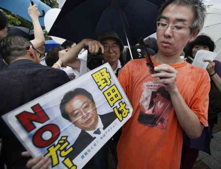 "Protesters stage a rally against the restart of a nuclear reactor, near Prime Minister Yoshihiko Noda's office in Tokyo, Friday, July 6, 2012. A nuclear reactor in western Japan begun generating electricity, Thursday July 5, in the first restart since last year's tsunami led to a nationwide nuclear power plant shutdown. The placard reads: ""No to Noda."" (AP Photo/Koji Sasahara)"