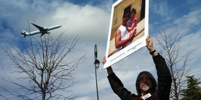 Un manifestant brandit un poster d'une personne expulsée lors d'un rassemblement en mars 2010 à l'appel d'une quinzaine d'associations près du centre de rétention administrative (CRA) du Mesnil-Amelot.